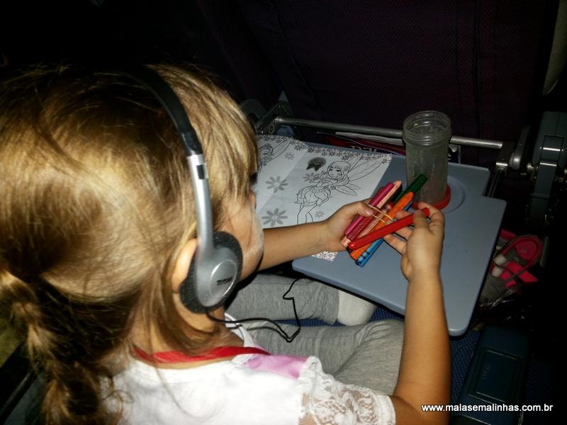 Beatriz desenhando e se divertindo com música no voo
